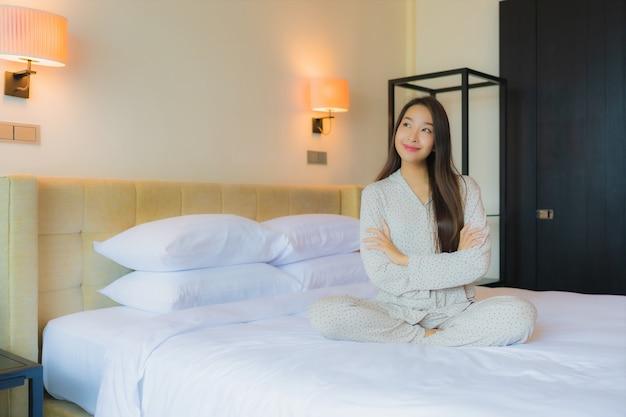 Retrato hermosa joven asiática sonrisa feliz relajarse en la cama