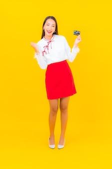 Retrato hermosa joven asiática con tarjeta de crédito para compras en línea en amarillo