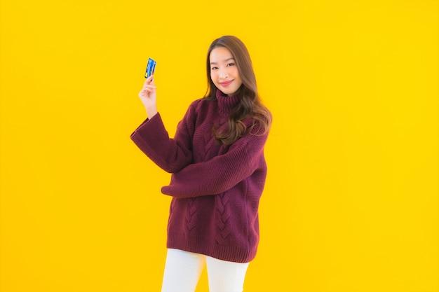 Retrato hermosa joven asiática con tarjeta de crédito para compras en línea
