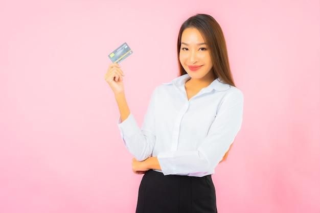 Retrato hermosa joven asiática con tarjeta de crédito en la pared rosa