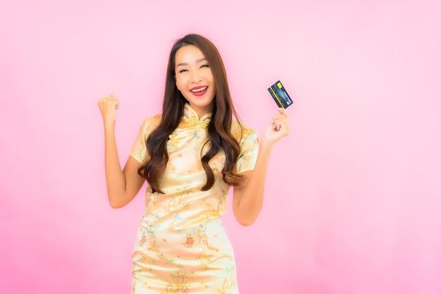 Retrato hermosa joven asiática con tarjeta de crédito y teléfono móvil en la pared de color rosa