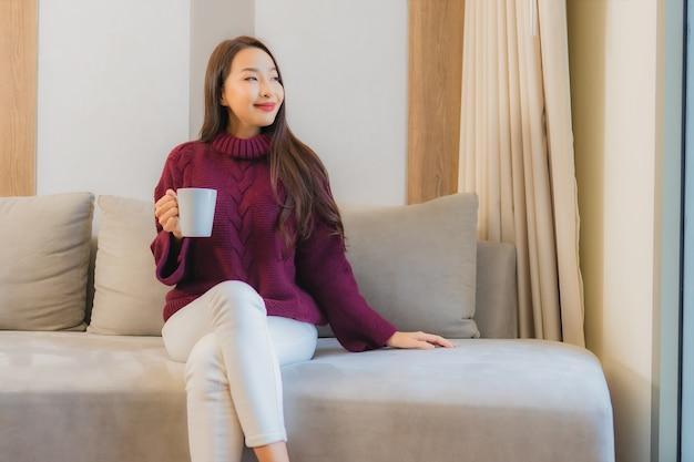 Retrato hermosa joven asiática con taza de café en el interior de la decoración del sofá de la sala de estar