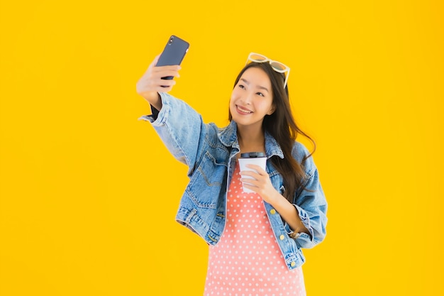 Retrato hermosa joven asiática con taza de café tomando selfie con smartphone