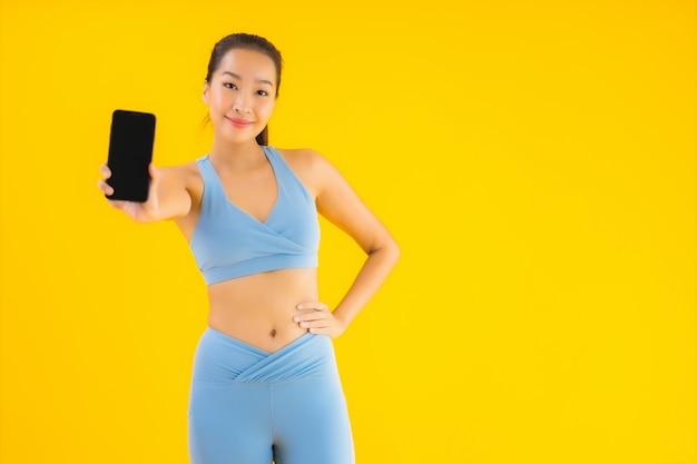 Retrato hermosa joven asiática con teléfono móvil inteligente en amarillo aislado