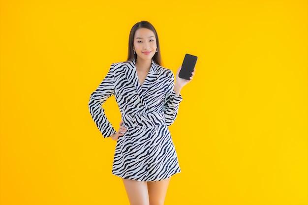 Retrato hermosa joven asiática con teléfono móvil inteligente y tarjeta de crédito en amarillo