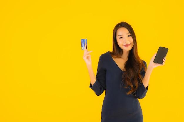 Retrato hermosa joven asiática con teléfono y tarjeta de crédito