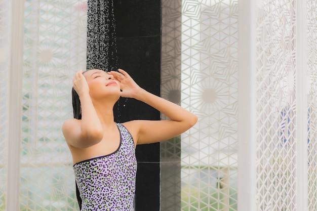 Retrato hermosa joven asiática tomar una ducha alrededor de la piscina al aire libre