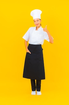 Retrato hermosa joven asiática en uniforme de cocinero o cocinero con sombrero sobre fondo amarillo aislado