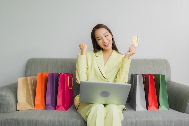 Retrato hermosa joven asiática usa computadora portátil con tarjeta de crédito para compras en línea en el sofá en el interior de la sala de estar