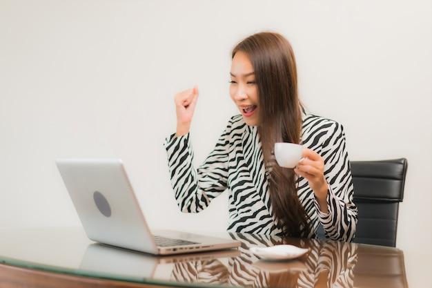 Retrato hermosa joven asiática usar computadora portátil en la mesa de trabajo en la habitación