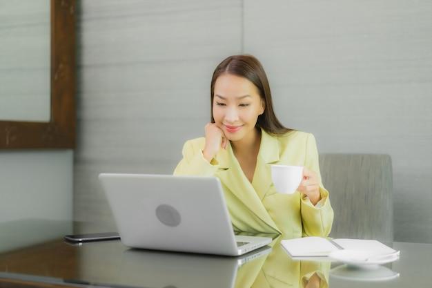 Retrato hermosa joven asiática usar computadora portátil con teléfono móvil inteligente en la mesa de trabajo en la habitación interior