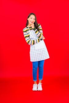 Retrato hermosa joven asiática usar delantal en la pared roja