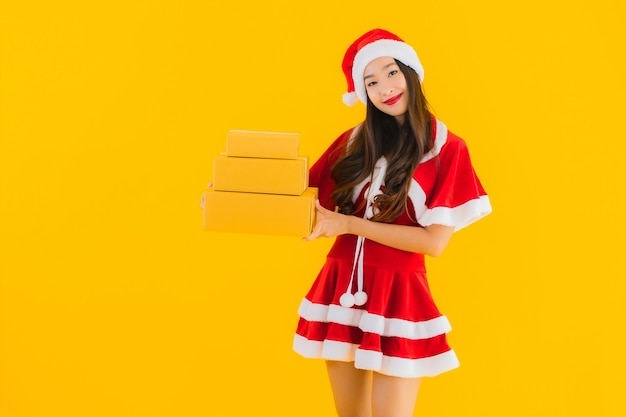 Retrato hermosa joven asiática usar ropa de navidad sombrero con caja de paquetería