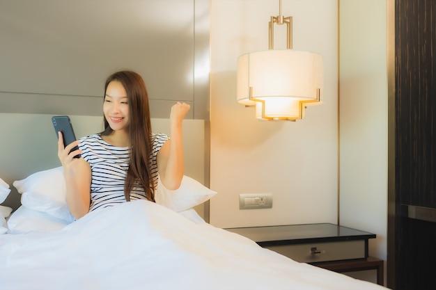 Retrato hermosa joven asiática usar teléfono móvil inteligente en la cama en el interior del dormitorio