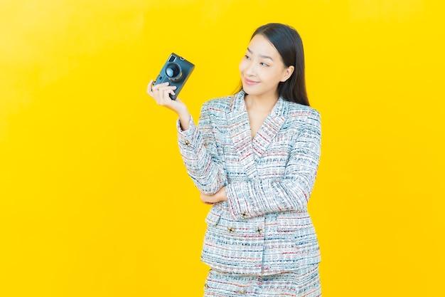 Retrato hermosa joven asiática use la cámara en la pared de color