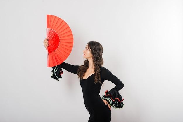 Retrato de hermosa joven bailando flamenco con ventilador en estudio