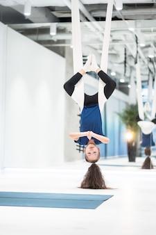Retrato de una hermosa joven dedicada a volar yoga en lienzos.