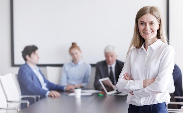 Retrato de hermosa joven empresario frente a su equipo en la oficina