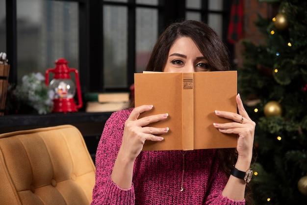 Retrato de una hermosa joven escondida detrás de un libro abierto.