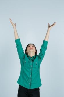 Retrato de hermosa joven estirando los brazos mientras mira hacia arriba con camisa verde y mirando agradecido vista frontal