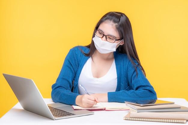 Retrato de una hermosa joven estudiando en la mesa con computadora portátil y portátil en casa - estudiando el sistema de e-learning en línea