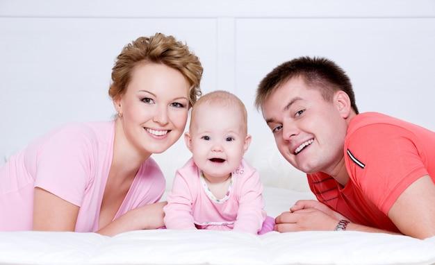 Retrato de la hermosa joven familia feliz acostado en la cama en casa