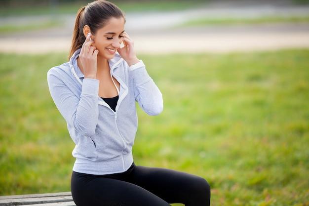 Retrato de una hermosa joven fitness escuchando música