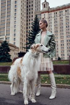 Retrato de una hermosa joven con galgo ruso