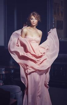 Retrato de una hermosa joven en el interior en un vestido rosa volando.
