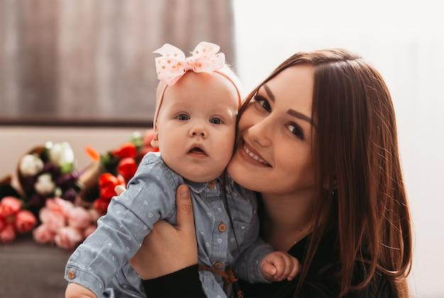 Retrato de una hermosa joven madre y niña infanta. una mirada a la camara