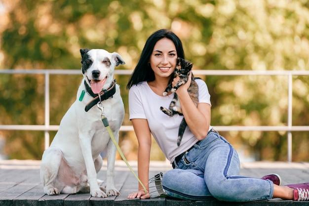 Retrato de la hermosa joven morena con pequeño gato y perro sabueso grande sentado al aire libre en el parque