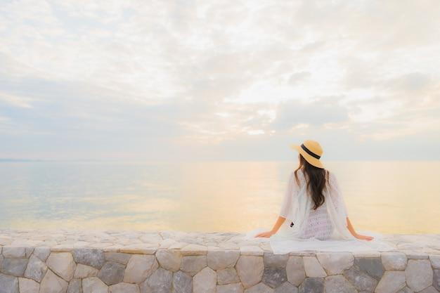 Retrato hermosa joven mujer asiática feliz sonrisa relajarse alrededor del mar playa océano