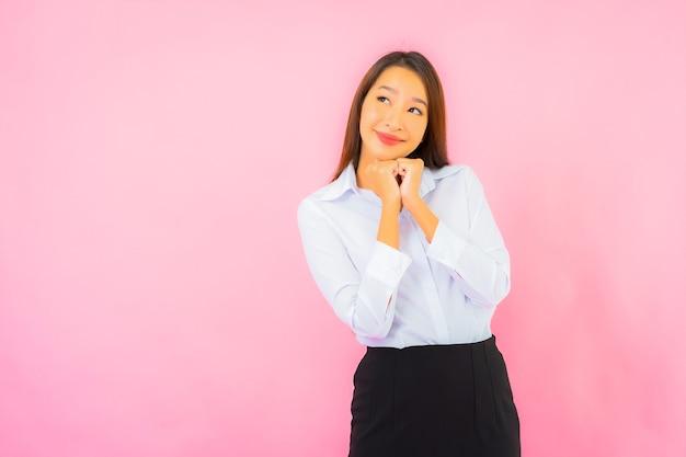 Retrato hermosa joven mujer asiática de negocios con acción rosa pared aislada