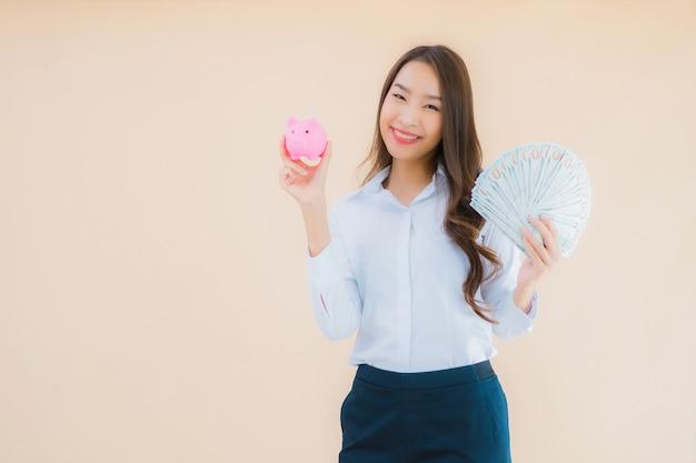 Retrato hermosa joven mujer asiática de negocios con dinero en efectivo o dinero