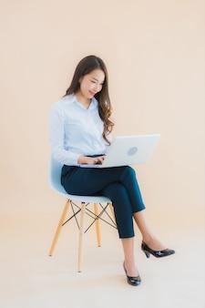 Retrato hermosa joven mujer asiática de negocios sentarse en una silla con ordenador portátil o teléfono inteligente para el trabajo