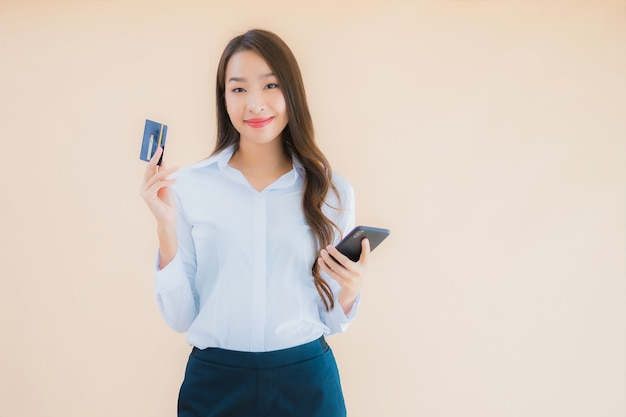 Retrato hermosa joven mujer asiática de negocios con teléfono y tarjeta de crédito