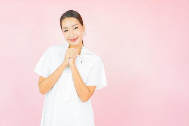 Retrato hermosa joven mujer asiática sonríe con mucha acción en la pared rosa
