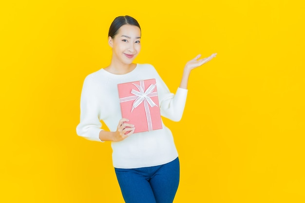 Retrato hermosa joven mujer asiática sonrisa con caja de regalo roja sobre amarillo