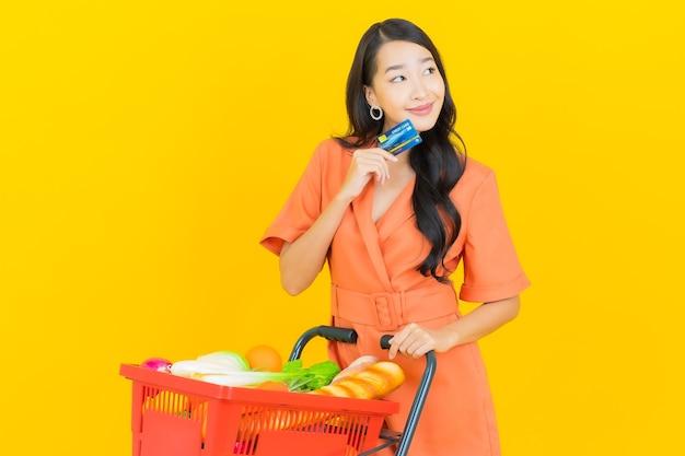 Retrato hermosa joven mujer asiática sonrisa con canasta de supermercado en amarillo