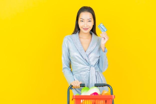 Retrato hermosa joven mujer asiática sonrisa con canasta de supermercado en pared amarilla