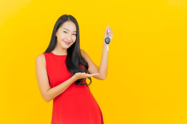 Retrato hermosa joven mujer asiática sonrisa con llave de coche en la pared amarilla