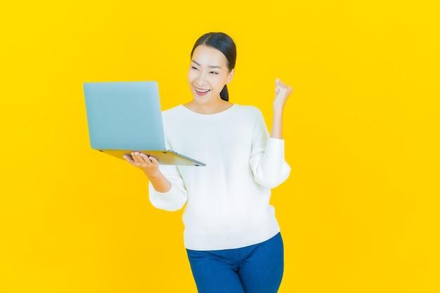 Retrato hermosa joven mujer asiática sonrisa con ordenador portátil en amarillo