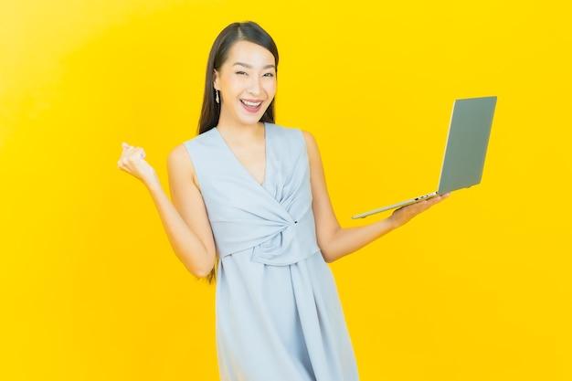 Retrato hermosa joven mujer asiática sonrisa con ordenador portátil sobre fondo aislado