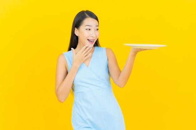 Retrato hermosa joven mujer asiática sonrisa con plato plato vacío en la pared de color amarillo