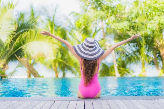 Retrato hermosa joven mujer asiática sonrisa relajarse alrededor de la piscina al aire libre en el hotel resort en viaje de vacaciones de vacaciones