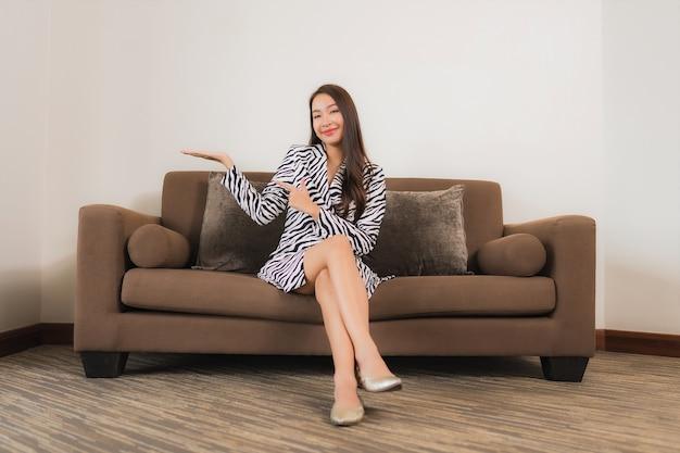 Retrato hermosa joven mujer asiática sonrisa relajarse en el sofá en el interior de la sala de estar