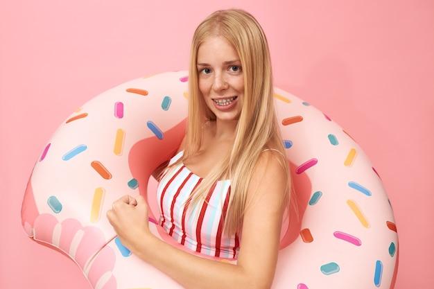 Retrato de hermosa joven mujer europea con cabello rubio y cuerpo en forma posando aislada con círculo de natación inflable, con expresión facial segura