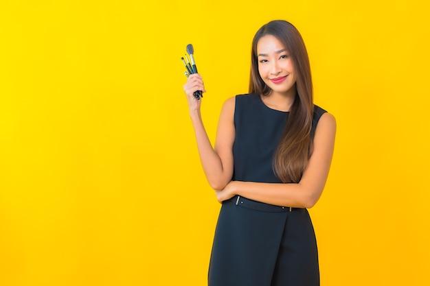Retrato hermosa joven mujer de negocios asiática con maquillaje cepillo cosmético sobre fondo amarillo