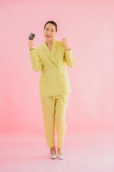 Retrato hermosa joven mujer de negocios asiática con tarjeta de crédito en color