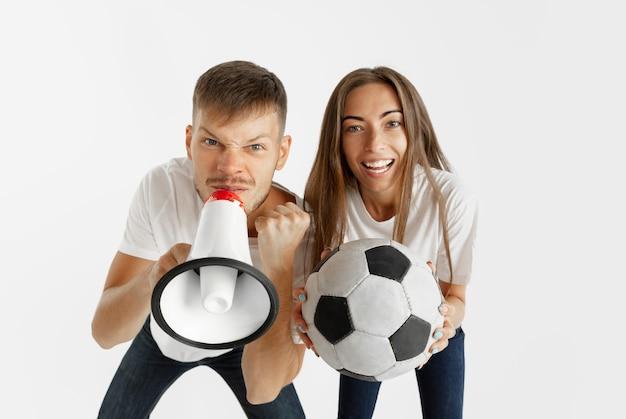Retrato de la hermosa joven pareja de aficionados al fútbol o al fútbol en la pared blanca. expresión facial, emociones humanas, publicidad, concepto deportivo. mujer y hombre saltando, gritando, divirtiéndose.